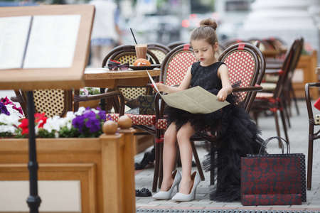 It is a cute little girl. Adorable little girl having lunch at an outdoor cafe. Girl alone in an outdoor cafe Archivio Fotografico