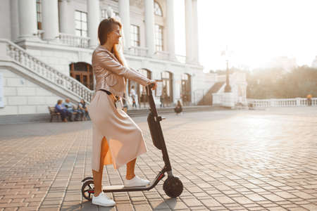 If you are a girl, you?ll be on the beach in the sunset. Walk on a kick scooter.Beautiful woman riding a scooter, walking, leisure, entertainment