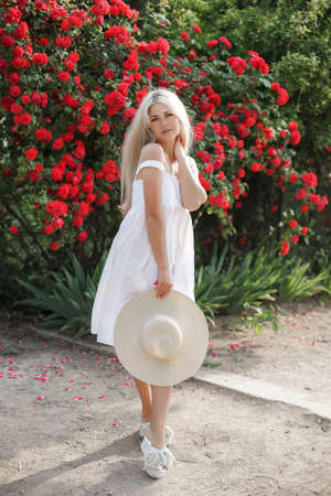 Perfume and cosmetics. Woman in front of blooming roses bush. Blossom of wild roses. Aroma of roses. Girl adorable blonde sniffing fragrance of pink bloom. Outdoors in the spring garden
