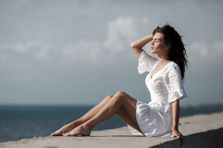 Beautiful girl in white dress on seacoast. Girl in summer white dress sitting on the shore.Beautiful slender thin girl sitting by the sea, enjoying the breeze. Young woman with beautiful long tanned legs.Travel and summer vacation