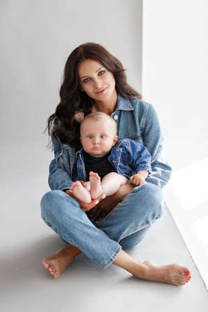 Young woman mother in denim overalls holds a baby child in her arms. White background in the studio.Mother with baby isolated on white. Mothers Day, love family, parenthood childhood concept. Happy family with newborn. Portret mother and little son.