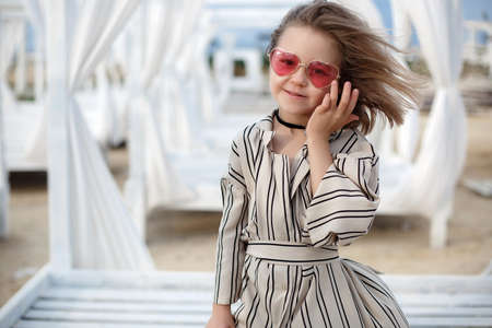 Small (8 years old) pretty cheerful girl in a white striped dress and in pink sunglasses stands on a wooden white pier. 8 years old girl resting on the tropical beach alone on a warm sunny day.Child posing on a tropical beach during summer vacations
