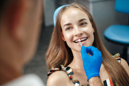 Dental clinic. Reception, examination of the patient. Teeth care. Young woman undergoes a dental examination by a dentist. Happy patient and dentist concept. Male dentist in dental office talking with girl patient.