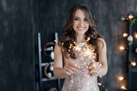 Beautiful girl in a dark room with sparklers in her hands on the night before Christmas. Portrait of a beautiful girl on New year's eve.Christmas interior in the background.Young and beautiful woman celebrating Christmas at home alone.
