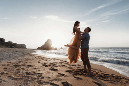 Couple in love at dawn by the sea. Honeymoon trip. Man and woman traveling. Happy couple by the sea view from the back. Man and woman holding hands. Couple in love on vacation. Follow me Couple on a rocky beach of blue ocean on a sunny day Stock Photo - 137069427
