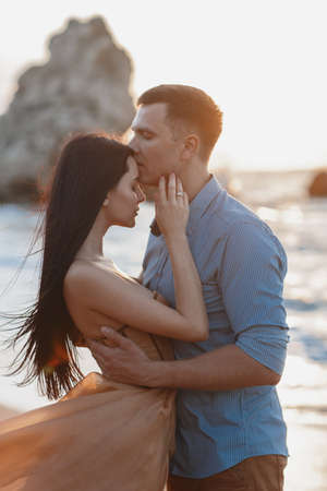 Couple in love at dawn by the sea. Honeymoon trip. Man and woman traveling. Happy couple by the sea view from the back. Man and woman holding hands. Couple in love on vacation. Follow me Couple on a rocky beach of blue ocean on a sunny day