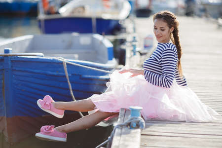 Happy young womanl with a long braid happy laughing while sitting outdoor with boats on background. Portrait of blissful smiling brunette woman having fun on city pier in sunny day. Girl in a striped T-shirt of a sailor on a wooden pier near the sea