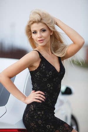 The elegant blonde beautiful woman posing near luxury vehicle. Foto de archivo