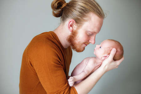 Closeup portrait of young bearded Caucasian father hugging and kissing newborn baby. Male man parent holding child. Authentic lifestyle touching tender moment. Single dad family life concept. Studio portrait of a happy father with a baby in his arms