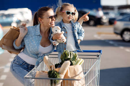 Mom and little daughter with ponytails, dressed in white T-shirts and blue jeans posing in the background of the parking lot near the supermarket with packages in hand. Mother and daughter shopping outdoors.