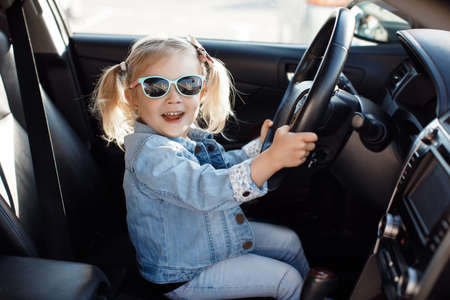 Cute little girl behind wheel of car. Baby girl sitting on the driver's seat in a family car. Child driving a passenger car. A child observes and tests a new car at a car dealership. A little girl sits in the driver's seat in the car.