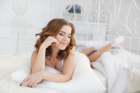 Smiling Young beautiful woman in the pajama wake up in the morning in the bedroom.Beautiful woman enjoying morning waking up in bed. Portrait of the beautiful young woman sleeping in white bed.