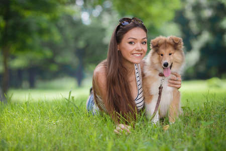 Beautiful woman in a summer park with her pet, collie puppy, outdoors on a sunny day. Smiling young attractive woman playing with cute collie puppy in summer garden or city park outdoors on green grass Stock fotó