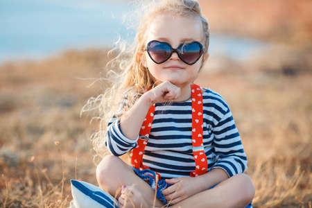 Happy little girl with long blond hair in a straw hat and sunglasses walks on a meadow at sunset with a seascape on the background. Ð¡hild plays alone in nature while sitting on dry grass near a pond.
