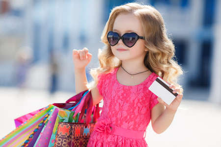 Beautiful happy smiling little girl child in sunglasses is holding shopping bags near shopping mall outdoors.Lifestyle concept.little shopaholic girl. girl with bags in hands.The delight of shopping.