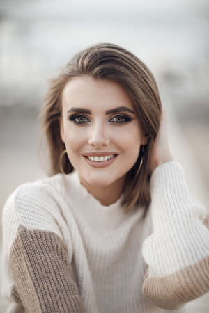 Young woman in a sweater on the sandy coast of an empty beach in the cool weather in early spring. Portrait of a beautiful young model enjoying the day on the background of a deserted beach
