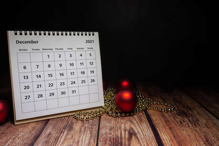 december 2021 calendar on wood with christmas decorations