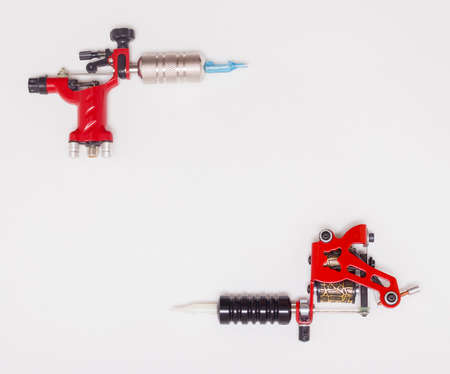 Rotary and induction tattoo machines on a white background, free space for text. The view from the top.
