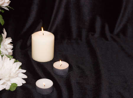 The concept of funeral service. Candles and white flowers on a black background. Free space for text. Stock Photo