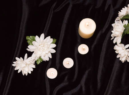 The concept of the memorial. Candles and white flowers on a black background, top view.