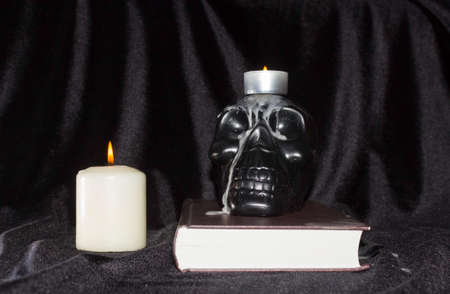 The concept of magic, occultism and esotericism. A black human skull on a book with candles on a black background.