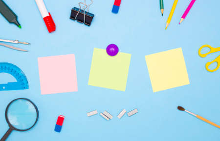 The concept of school and students. Three empty square of colored paper for notes in the middle. School and office stationery on the edges on a blue background. Top view, free space for text.
