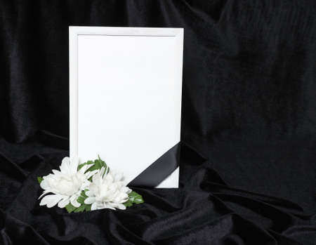 Condolence card. Memorial frame with black ribbon. White flowers. Black background. Stock Photo
