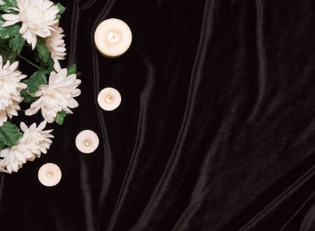 The concept of the memorial. Candles and white flowers on a black background, top view. Free space for text. Stockfoto