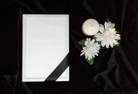 Condolence card. Memorial frame with black ribbon. White flowers and a burning candle. Black background. Stock Photo