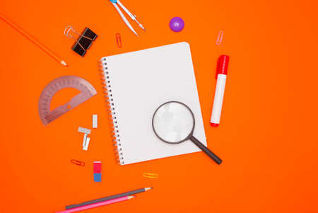 The concept of training and education. An empty checkered notebook and stationery on an orange background.