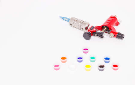 Rotary tattoo machine and color paints in disposable plastic jars on a white background. Free space for text. Side view.