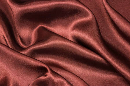 Smooth elegant brown silk or satin luxury cloth texture can be used as abstract background. Crumpled fabric Twisted at the side.