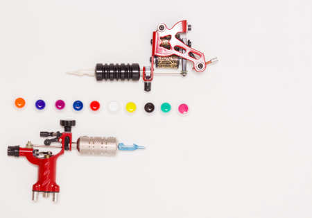 Rotary and induction tattoo machines and color paints in disposable plastic jars on a white background. Free space for text. The view from the top.