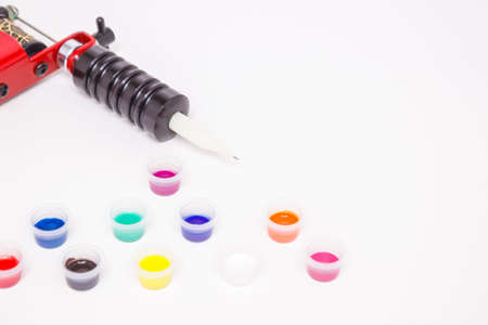 Part of the induction tattoo machine and colored paint in disposable plastic jars on a white background. Free space for text. Tattoo equipment. Side view.