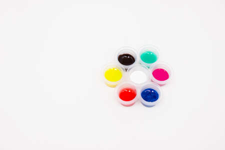 Colored paints in plastic jars in a circle on a white background. Free space for text. The view from the top.