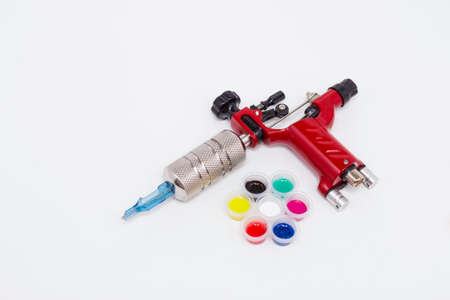Rotary tattoo machine and color inks in disposable plastic cans on a white background. Free space for text. Tattoo equipment. Side view.