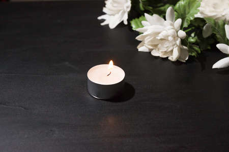 Funeral symbol. A burning candle on a black background, a bouquet of white flowers in the background. Side view.