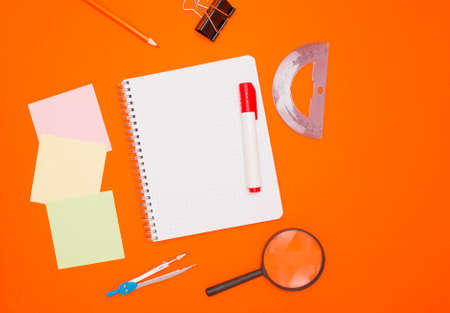 The concept of training and education. Three empty square notes, an empty checkered notebook, and office supplies on an orange background. The view from the top. 版權商用圖片