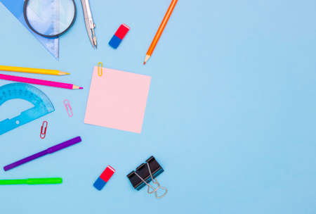 The concept of school and students. Empty square colored paper for writing in the middle. School and office stationery on the edges on a blue background. Top view, free space for text.