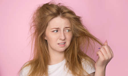The concept of dry lifeless hair. A woman on a pink background holds her disheveled, tangled hair and looks at it with a discontented expression.