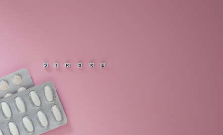 Concept of health, cardiology, heart disease. Words STROKE on white cubes, tablets in blisters on a pink background. Flat lay, copyspace.