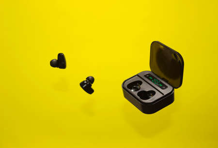 Levitation, black wireless headphones and charger - a container for headphones on a bright yellow background.