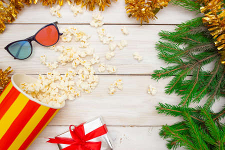 The concept of cinema, New Year and Christmas. Popcorn spills out of the box, green Christmas tree branches and 3D glasses. Light wooden background, top view.