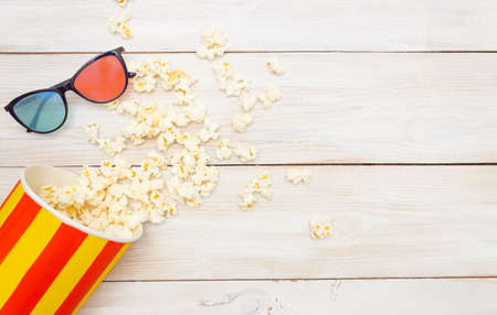 Concept movie preview of the film. Popcorn spills out of the box and 3D glasses. Light wooden background, free space for text, top view.