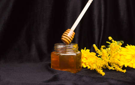 Bee honey drips from a wooden spatula into a glass jar. Yellow flowers, black background. Useful farm products.