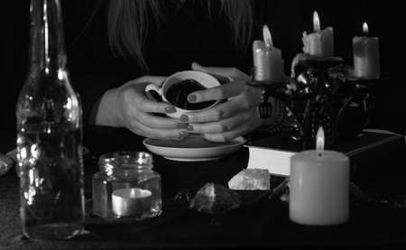 Fortune-telling on coffee grounds. A fortune teller's hands, a Cup of coffee, candles, and skulls on a black table. The concept of wizards, witchcraft and magic.