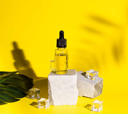 Cosmetic oil for hair or face in a glass bottle with a pipette. Body care, spa. Trending colors, shadows, and ice cubes.