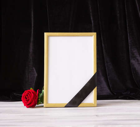 The concept of memory, funerals and condolences. Photo frame with black mourning ribbon and flower.