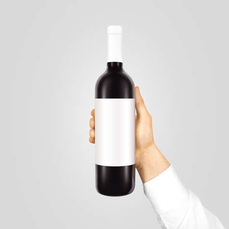 sticker: Blank white label mock up on black bottle of red wine in hand isolated. Alcohol bottle mockup presentation ready for design. Full drink bottle template with empty sticker. Clear tag vine bottle. Stock Photo