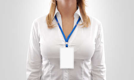 Woman wear blank white vertical badge mockup, stand isolated. Name tag on neck and chest. Person identity label. Women in shirt uniform with empty id card mock up.  Bussinesswoman pass design.